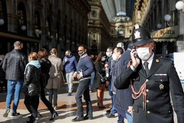 """Associated Press A traffic policeman talks on the phone at the Vittorio Emanuele II arcade in Milan, Italy, Friday. Italian health officials have declared the country in an """"acute phase"""" of the coronavirus pandemic after the country set records for new daily cases."""