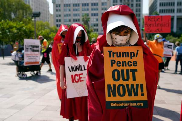 Associated Press photos Demonstrators wear costumes and hold signs during a Women's March in Los Angeles, one of several held across the nation.