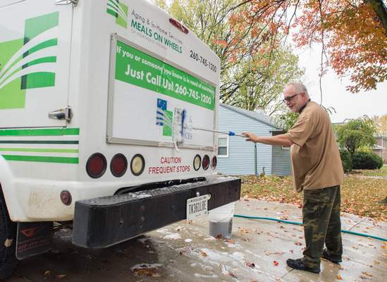 Michelle Davies | The Journal Gazette Dennis Scriven takes advantage of the weather and washes his work vehicle Thursday morning.