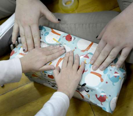 Journal Gazette file In this 2015 photo, a kindergartner and high school freshman wrap a gift together at Concordia High School for a family adopted through the Allen County Christmas Bureau.