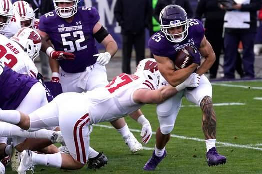 Associated Press Northwestern running back Isaiah Bowser is tackled by Wisconsin linebacker Jack Sanborn during the first half Saturday in Evanston, Ill.