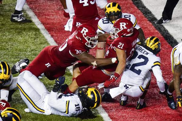 Frank Franklin II | Associated PressRutgers' Johnny Langan (21) rushes against Michigan's Luiji Vilain (18) and Gemon Green (22) for a touchdown during the first half of an NCAA college football game Saturday, in Piscataway, N.J.