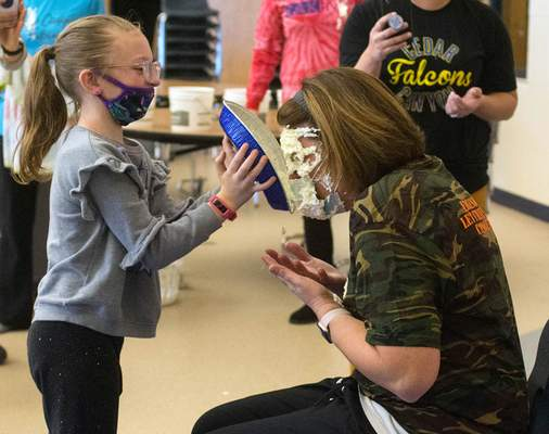 Photos by Michelle Davies | The Journal Gazette Paisley Carter, a second grader at Cedar Canyon Elementary School, puts a pie in the face of school nurse Betsy Bloom on Friday afternoon as part of a school fundraiser.