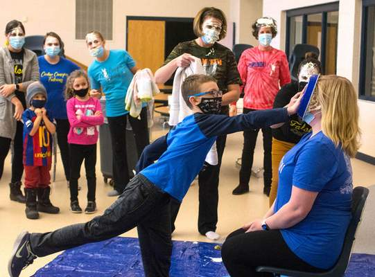 """Will Rauch, a Cedar Canyon fourth grader, smashes a pie in the face of Sarah Hartman, a Northwest Allen County Schools social worker, on Friday afternoon. Eight randomly selected students were awarded the honor """"delivering"""" pies to teachers, staff and the school principal as a result of raising $3,500 for the Leukemia & Lymphoma Society."""