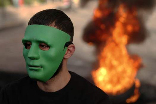 Associated Press Tires blocking a road burn behind a masked protester Thursday in Beirut, where an economic crisis has prompted a new wave of protests.