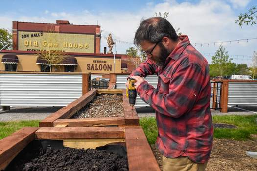 Michelle Davies | The Journal Gazette Matt Deacon, with Don Hall's, works on finishing up galvanized planters Friday morning downtown in preparation for The Deck's opening, scheduled for Tuesday.
