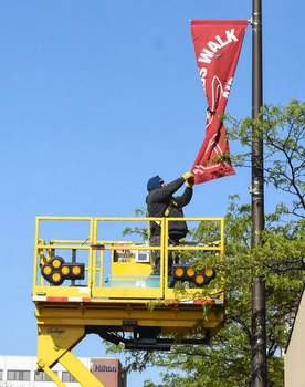 Michelle Davies | The Journal Gazette Adam Butler, a sign fabricator with Traffic Operations, hangs banners along East Washington Boulevard on Friday morning.