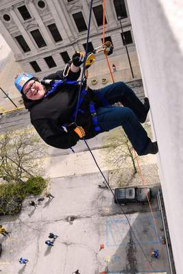 Photos by Michelle Davies | The Journal Gazette A team from UAW Local 2209, which included Amanda Meier, above, president of the UAW Cap Council, and Courtney Lewis takes part in Over the Edge on Friday morning. Participants rappelled down the side of the PNC building with proceeds going to the Strong Neighborhoods Initiative, which aims to bring resources to neighborhoods in Fort Wayne.