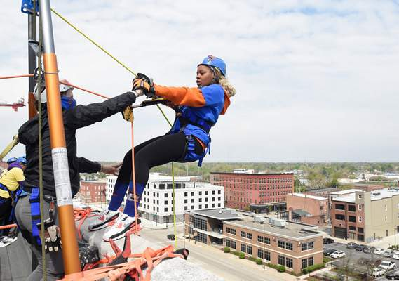 Photos by Michelle Davies | The Journal Gazette A team from UAW Local 2209, which included Amanda Meier president of the UAW Cap Council, and Courtney Lewis, above, takes part in Over the Edge on Friday morning. Participants rappelled down the side of the PNC building with proceeds going to the Strong Neighborhoods Initiative, which aims to bring resources to neighborhoods in Fort Wayne.
