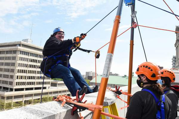 Michelle Davies | The Journal Gazette Amanda Meier, President of the UAW Cap Council, with a team from UAW Local 2209, takes part in Over the Edge Friday morning.  Participants rappelled down the side of the PNC building with all proceeds going to the Strong Neighborhoods Initiative.  The goal of the initiative is to help bring resources to neighborhood communities in Fort Wayne.