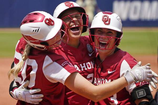 Sue Ogrocki | Associated PressOklahoma's Jayda Coleman, center, celebrates at home plate with teammates Jana Johns, left, and Grace Lyons, right, following her home run against Florida State in the second inning of the final game of the NCAA Women's College World Series softball championship series Thursday, in Oklahoma City.