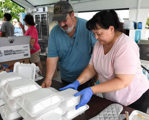 Michelle Davies | The Journal Gazette Jeff and Diana Massucii, of Fort Wayne, volunteers with Fort Wayne Turners and Germanfest, box meals at Saturday's drive thru Germanfest at Student Life Center on the Ivy Tech Community College.  THe boxed meals contained bratwurst in a bun, traditional sauerkraut, German potato salad and apple kuchen (strudel).