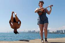 """Associated Press Dan O'Conor, the """"Great Lake Jumper,"""" makes his daily dip into Lake Michigan while local artist Plucky Rosenthal serenades with her ukulele Friday in Chicago's Montrose Point."""