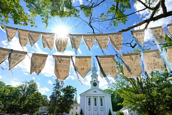 Associated Press Flags inscribed with names of people who have died from COVID-19 are displayed outside First Congregational Church in Holliston, Mass.