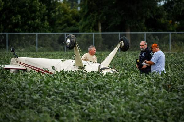 Mike Moore | The Journal Gazette Members of the Fort Wayne Police Department respond to a small-plane crash Saturday at Smith Field. The pilot walked away unhurt.