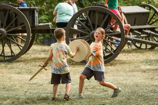 Mike Moore   The Journal Gazette Sarah McDowell, 7, sword-fights brother Matthew, 5, while attending the Johnny Appleseed Festival with their grandmother, Carla Stewart, on Saturday. The festival returned to its namesake park next to Memorial Coliseum after a year off due to the coronavirus pandemic.