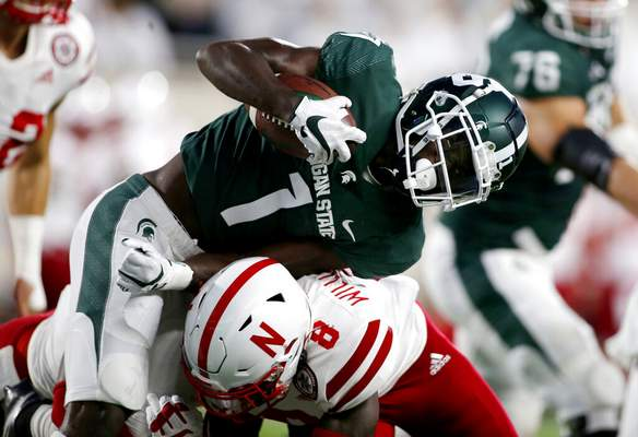 Al Goldis | Associated PressMichigan State's Jayden Reed, top, is stopped by Nebraska's Deontai Williams (8) during the first quarter of an NCAA college football game, Saturday, in East Lansing, Mich.