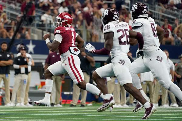 Associated Press KJ Jefferson, left, is chased by Texas A&M players Demani Richardson, middle, and DeMarvin Leal on Saturday in Arlington, Texas.