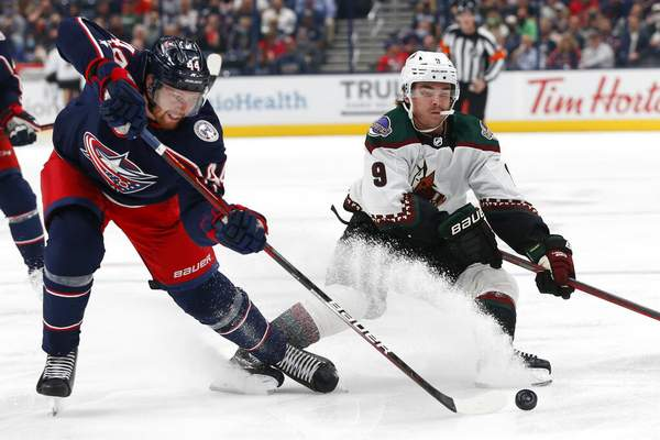 Jay LaPrete | Associated PressColumbus Blue Jackets' Vladislav Gavrikov, left, tries to clear the puck past Arizona Coyotes' Clayton Keller during the first period of an NHL hockey game Thursday, in Columbus, Ohio.