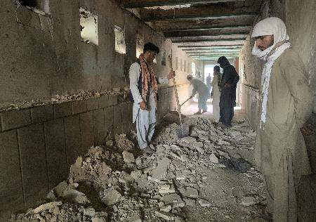 Associated Press People look at the inside of a mosque Friday in Kandahar, Afghanistan, after a deadly suicide bombing.