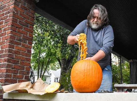 Michelle Davies   The Journal Gazette Wayne Hartman cleans out a pumpkin on the front porch of his Columbia Avenue home Friday afternoon.