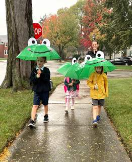 Terri Richardson | The Journal Gazette Deirdre Goshert walks her children William, 6, Ella, 3, and Eddie, 4, to school Friday morning. It was a wet walk to St. John the Baptist along West Sherwood Terrace, but the siblings had their frog umbrellas to help. A record 1.84 inches of rain fell Friday.
