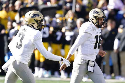 Charlie Neibergall | Associated PressPurdue quarterback Aidan O'Connell (16) celebrates with teammate wide receiver David Bell (3) after scoring on a 6-yard touchdown run during the first half of an NCAA college football game against Iowa, Saturday, in Iowa City, Iowa.