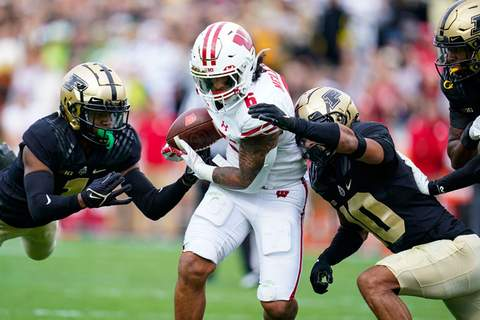 Associated Press Wisconsin running back Chez Mellusi is tackled by Purdue cornerback Dedrick Mackey, left, and safety Cam Allen during Saturday's game in West Lafayette.